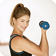 White woman smiling while lifting a dumb bell.
