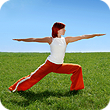 Woman doing a Tai Chi pose on a grassy field.